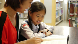 4K UHD : Little Asian students and teacher reading book in library together Live Action