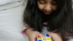 4K Video : Little Asian Girls Playing Rubik Cube On The Bed, Tilt Down stock footage