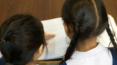 4K UHD : Top view of little Asian students with uniform reading book in library Footage