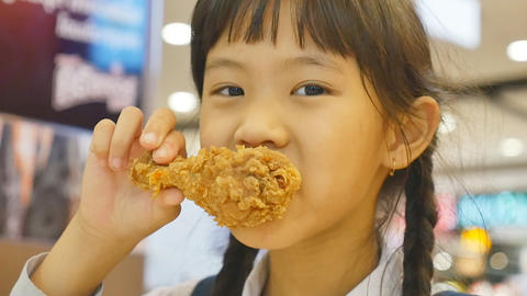 Asian child enjoys eating fried chicken Footage