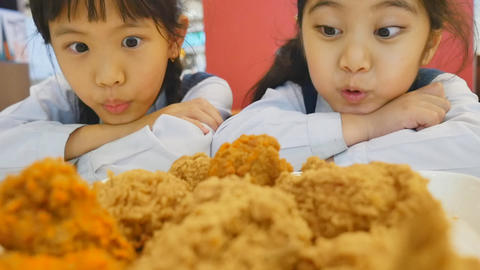 Slow motion of Happy Asian girls with fried chicken in restaurant, Tilt up Footage