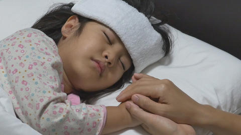 Asian child sick and sleeping on the bed with her mother by her side Footage