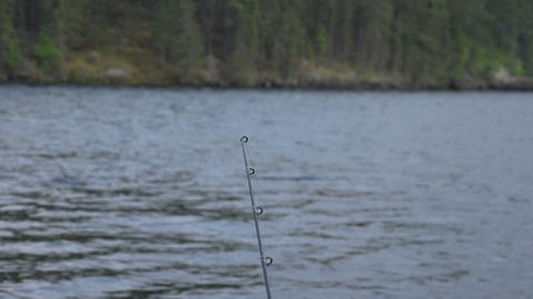 Fishing Rod Rack Focus To Wooded Shoreline stock footage