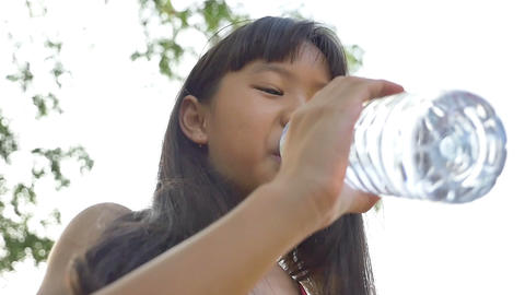 Little Asian Child drinking water in the park, Slow motion Footage
