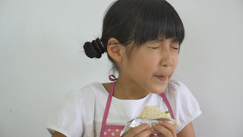 Slow motion of little Asian child eating delicious sandwich Footage