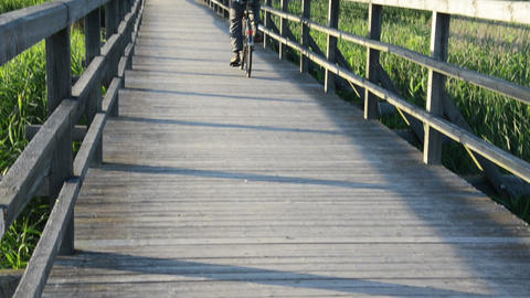 senior old man with cap drive bicycle wooden long bridge lake Footage