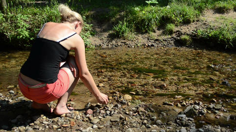 woman shorts sit stream throw pebble stones flowing water Footage