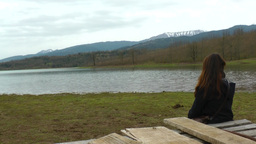A Girl Is Sitting Next To A Lake And Enjoying The View stock footage