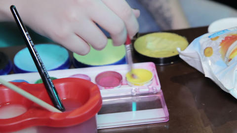 Woman draws with watercolors at the table Live Action