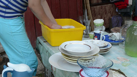 hands wash dirty dishes on rural village outdoor table Footage