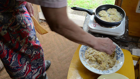 old woman bake cook potato pancake in rural house kitchen Footage
