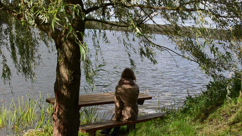 woman girl sit wooden bench willow tree move wind lake relax Footage