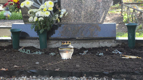 candle glass pot burn flowers near grave cemetery graveyard Footage