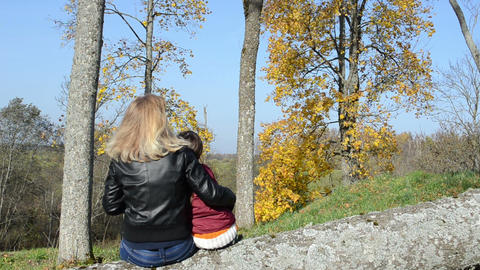 woman mother sit cut tree trunk daughter admire autumn tree Footage