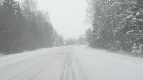 car go on forest road in winter snowstorm. snow falling Footage
