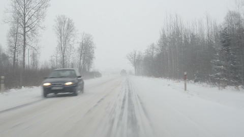 cars going slippery rural road winter snow snowstorm falling Footage