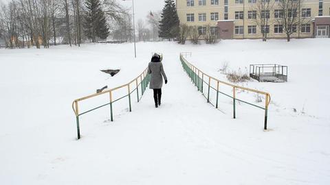 woman coat walk frozen river bridge winter snowstorm snow fall Footage