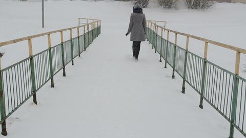 woman coat walk frozen river bridge winter snow fall Footage