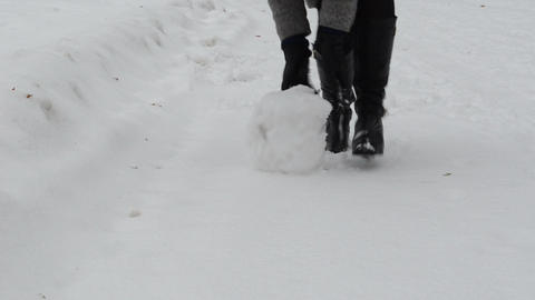woman rolling snowball snow ball make snowman winter park Footage