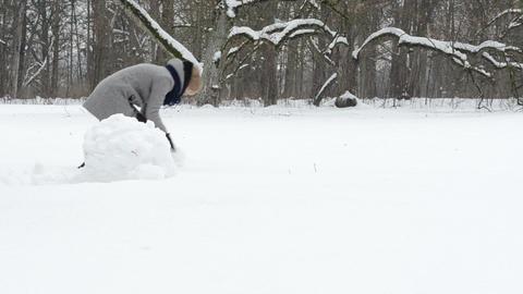 couple man woman roll snowball snow ball snowman winter park Footage