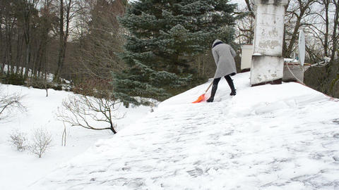 woman worker heel shoe coat clean snow house roof winter danger Footage