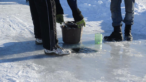 man draw water frozen ice hole pour bucket winter skate site Footage