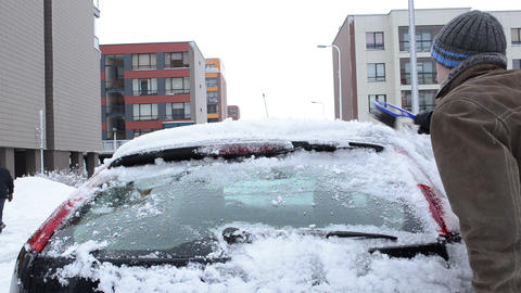 man clean remove snow car parking flat house winter season Footage