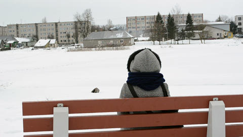 woman bench houses frozen snow river shore smoke chimney winter Footage