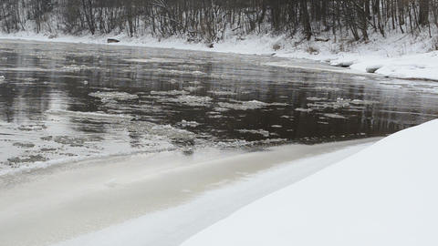forest river bay bank cover snow ice floe floating water winter Footage