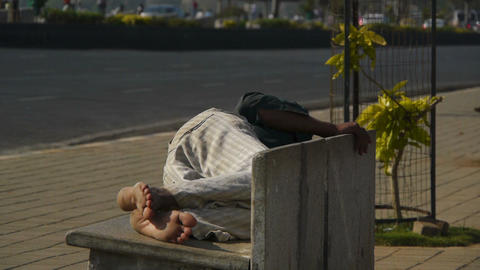 Man sleeping on a street bench Stock Video Footage