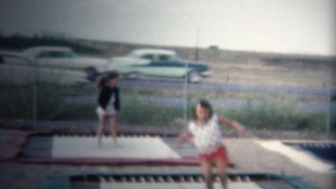 (8mm Vintage) 1962 Trampoline Jumping Busy Highway Behind Footage