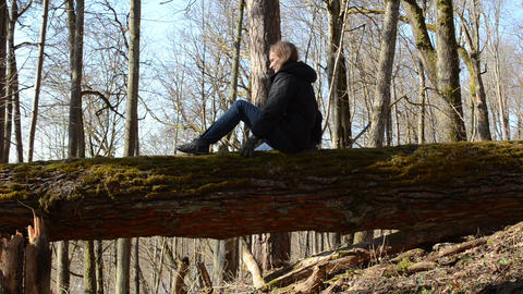 Girl Sitting On A Log In Forest Twisted Gently To The Other Side stock footage