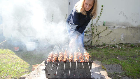 blond woman bake shashlik meat spit ember outdoor barbeque smoke Footage