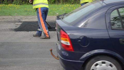 workers shovel put hot asphalt on road holes street repair Footage