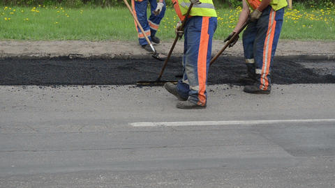Workers shovels special tools leveling hot asphalt road hole Footage