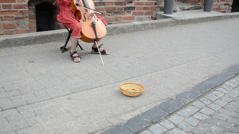 girl play with violoncello in old town. wicker dish money Footage