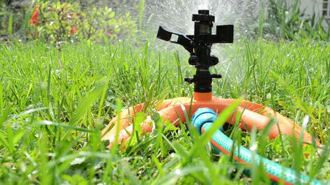 Sprinkler flower watering tool spray water drops on garden lawn Footage