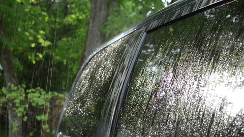 Strong rain water drops fall and splash on car roof and windows Footage