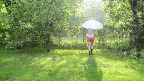 girl in shorts and gumboots walk with umbrella in rainy day Footage