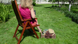 Botanist woman on wooden chair check dried leaves in old book Footage
