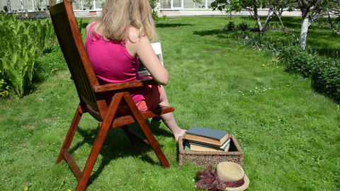 Woman in shorts read study thick book on wood chair Footage