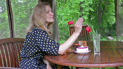 Woman in spotted dress smell red tulip flowers in vase and smile Footage