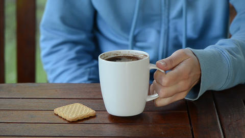 Hand put cup of steaming hot morning coffee near cookie on table Footage