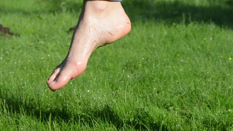 Dewy water drops on wet barefoot foot walking in morning meadow Footage