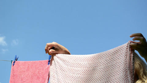 attractive woman hanging washed laundry on clothes-line and clip Footage