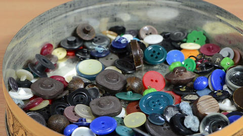 Closeup of different colorful buttons falling into box Footage
