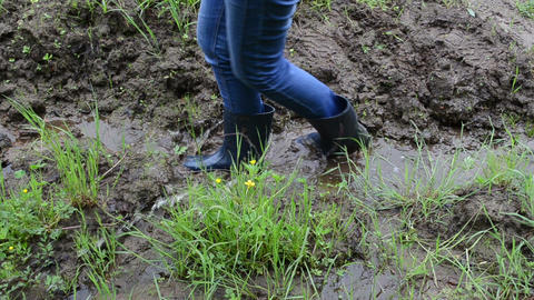 Woman legs with gumboots walk on wet dirt mud leaves foot prints Footage