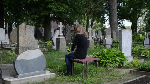 depressed woman sit on bench near father grave in cemetery Footage