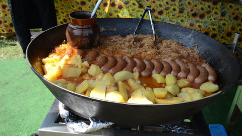 Potatoes, sausage and cabbage meal baked in a huge metal pan Footage