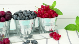 Plums, Red Currants And Blueberries In Small Metal Bucket stock footage